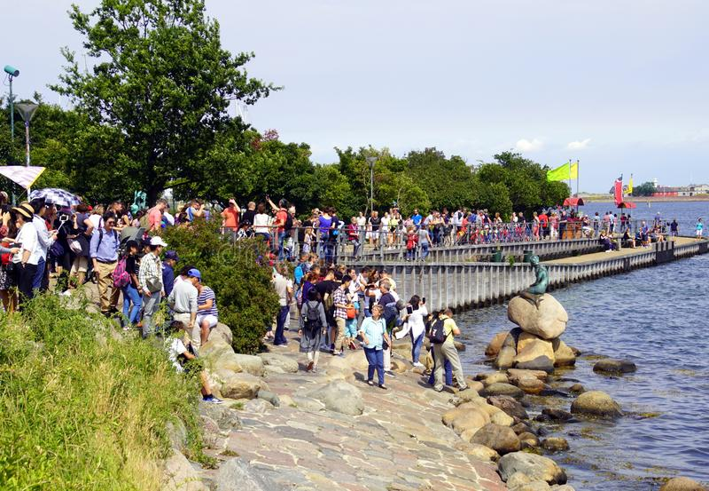 游人在哥本哈根为小的美人鱼雕象照相 库存图片