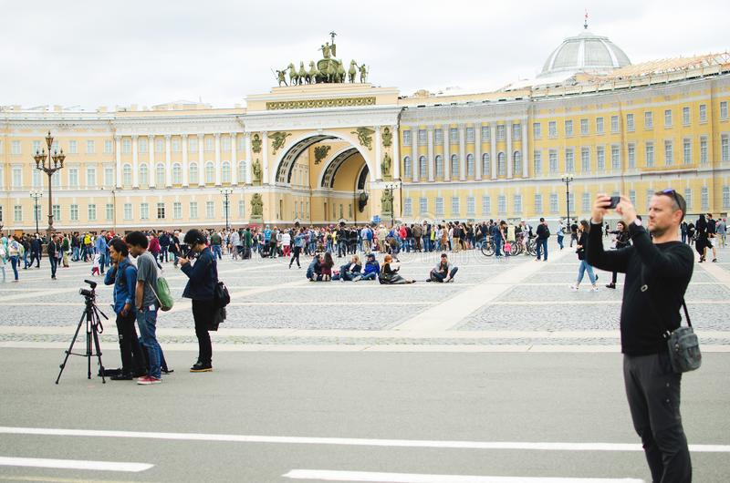 游人在圣彼德堡为在宫殿正方形的视域照相 库存图片