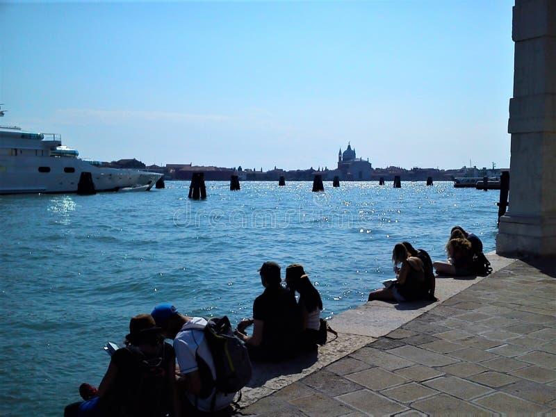 游人在威尼斯市,意大利 好日子、旅行、明亮的海和小船 免版税图库摄影