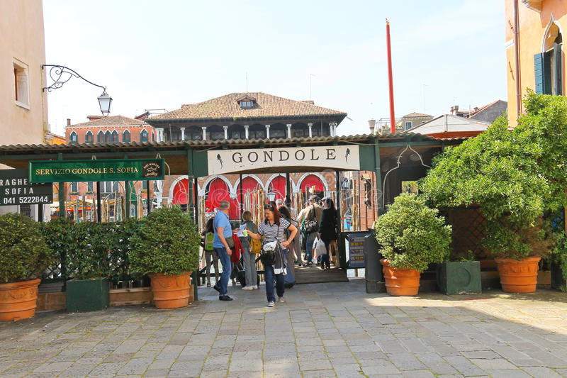游人在威尼斯,意大利临近在运河的长平底船服务 免版税库存图片