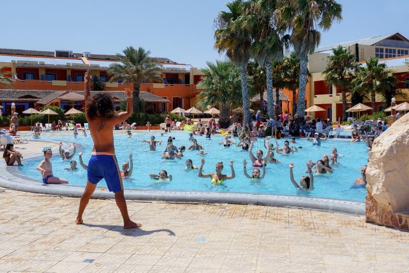 游人在度假做着在水池的水上体操 免版税图库摄影