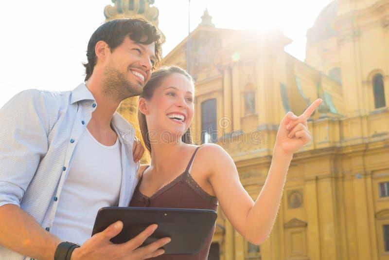 年轻游人在有片剂计算机的城市 免版税库存图片