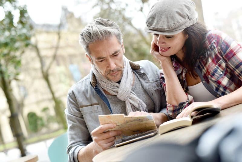 游人在看城市指南的镇里 免版税库存照片