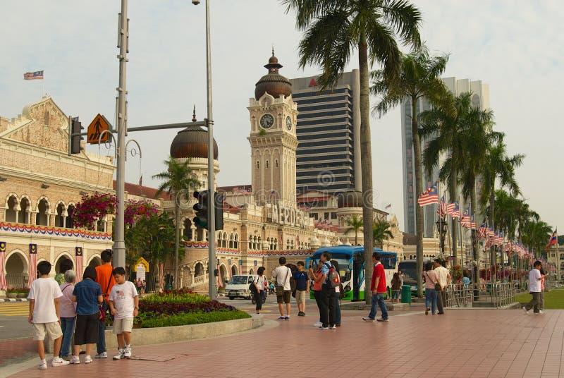 游人在苏丹阿卜杜勒萨玛德大厦前面走在独立正方形在吉隆坡,马来西亚 免版税库存照片