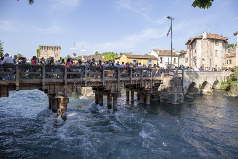 游人在Borghetto过在明乔河河的桥梁 免版税库存照片