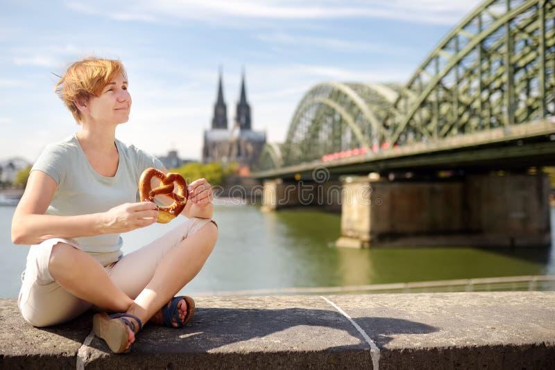 游人在Koel吃传统椒盐脆饼坐莱茵河的堤防在科隆主教座堂和霍亨索伦桥梁背景的  免版税库存照片