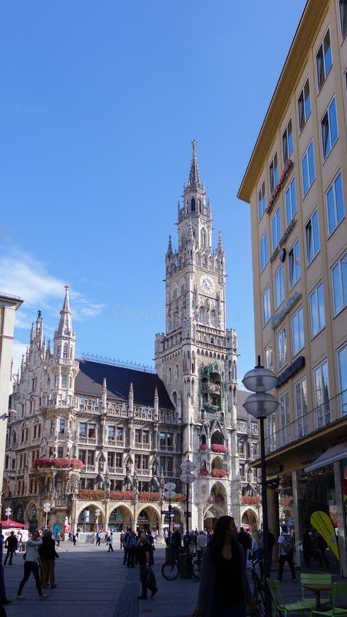 游人在Marienplatz在背景中摆正与Neues Rathaus 免版税库存图片