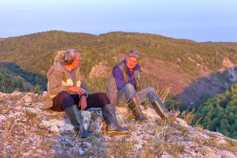 游人坐岩石小山的上面 图库摄影