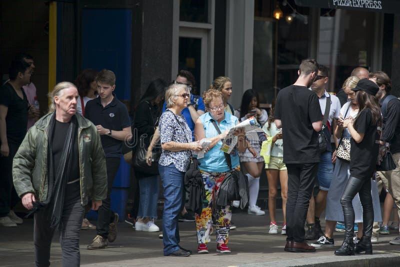 游人大人群在皮卡迪利广场地区 一对年长夫妇考虑城市的地图 库存图片