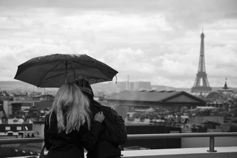 游人夫妇在雨天之前有埃佛尔铁塔背景 图库摄影