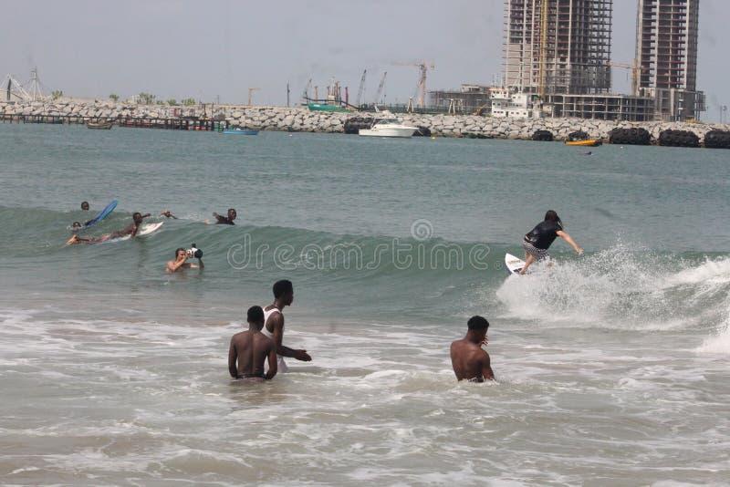 游人将喜欢冲浪在拉各斯海滩,钦佩者看  免版税库存照片