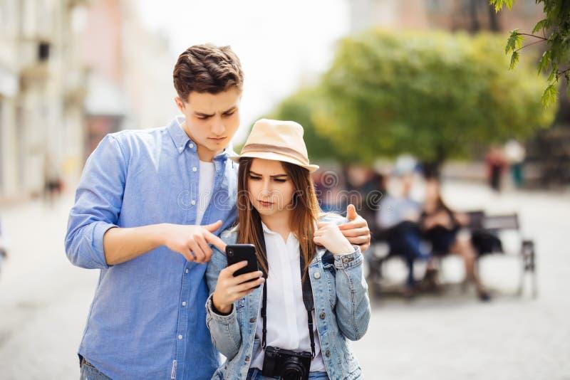 游人年轻夫妇画象在使用手机的镇在新的城市 免版税库存图片
