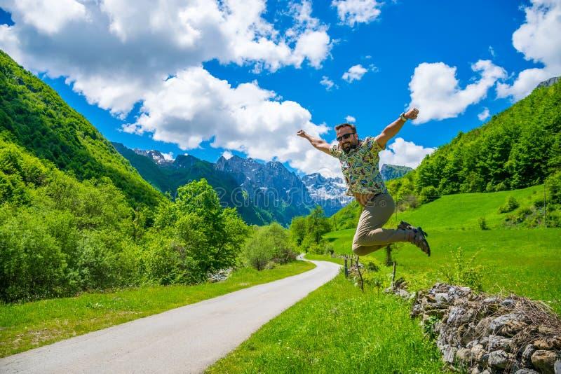 游人快乐跳以积雪覆盖的山为背景 免版税图库摄影