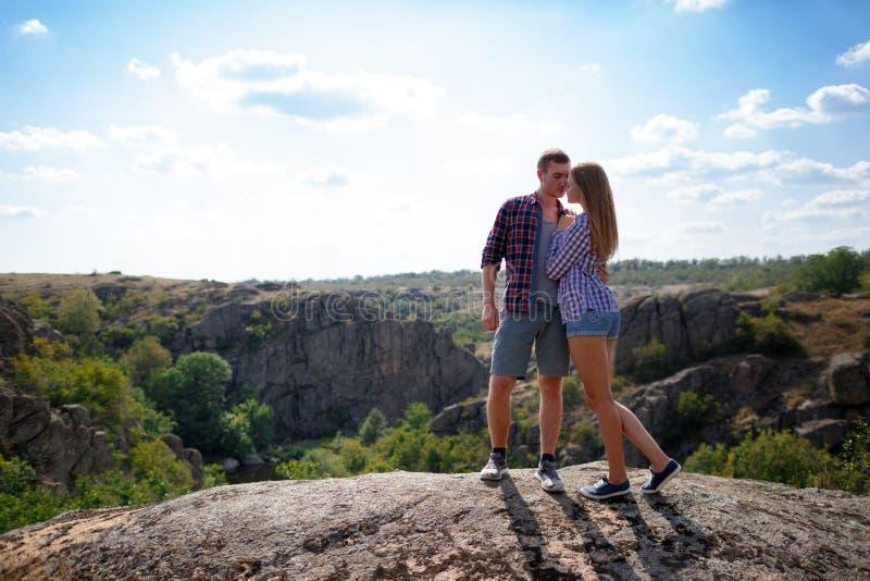 游人愉快的夫妇在山休息 一对爱恋的夫妇坐山并且享受美丽的景色 免版税库存照片