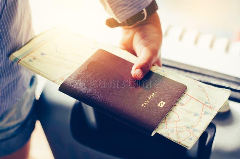 游人把柄护照和手提箱为旅行做准备 免版税库存照片