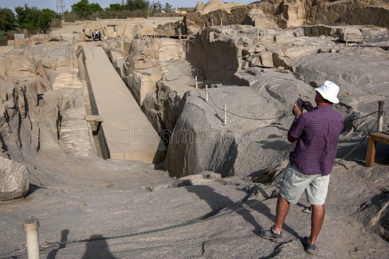 游人拍摄未完成的方尖碑的照片在古老西部猎物靠近阿斯旺在埃及 免版税库存照片