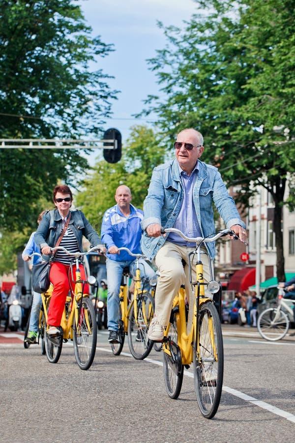 游人探索出租自行车的,阿姆斯特丹,荷兰城市 免版税库存照片