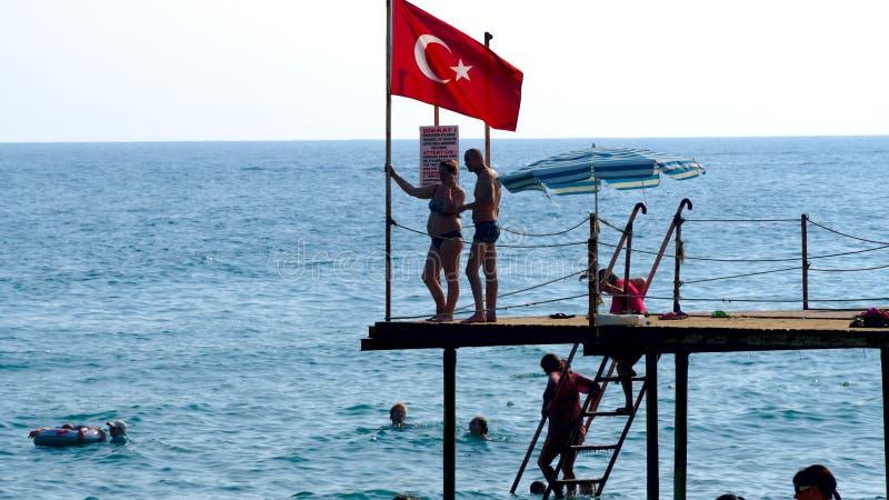 游人是在码头的海滩附近 免版税库存图片