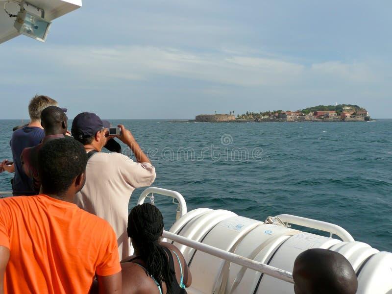 游人查阅塞内加尔的从小船的Goree海岛 库存照片