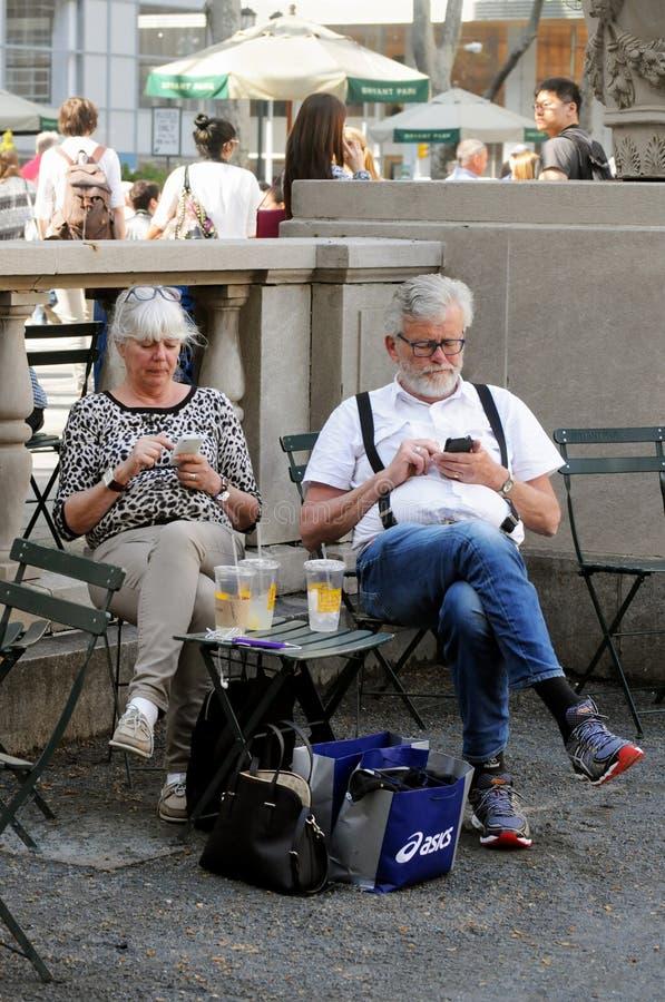 游人检查手机在纽约 免版税库存照片