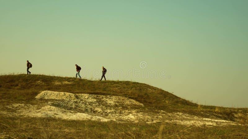 游人沿小山的上面走 商人联合工作  旅客队去胜利和 免版税库存照片