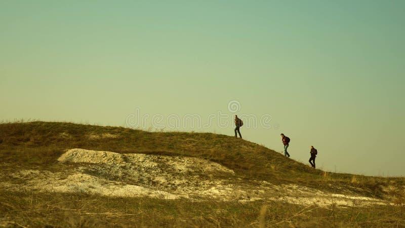 游人沿小山的上面走 商人联合工作  旅客队去胜利和 免版税库存图片