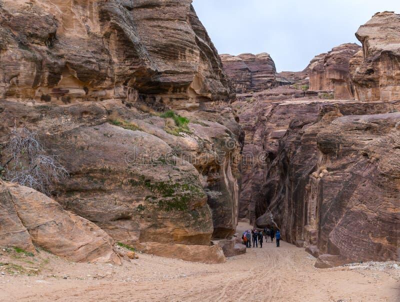 游人沿峡谷导致Petra的- Nabatean王国的资本走在旱谷芭蕉科市在约旦 免版税图库摄影
