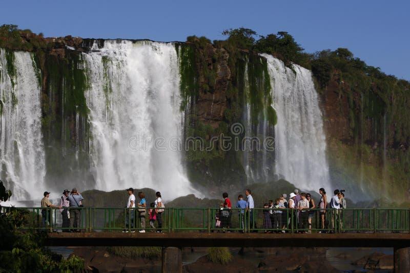 游人沿木板走道走在壮观的伊瓜苏瀑布在巴西 免版税图库摄影