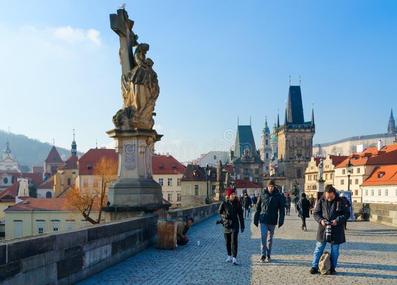 游人沿著名中世纪查理大桥走在清楚的晴朗的冬日,布拉格,捷克 库存图片