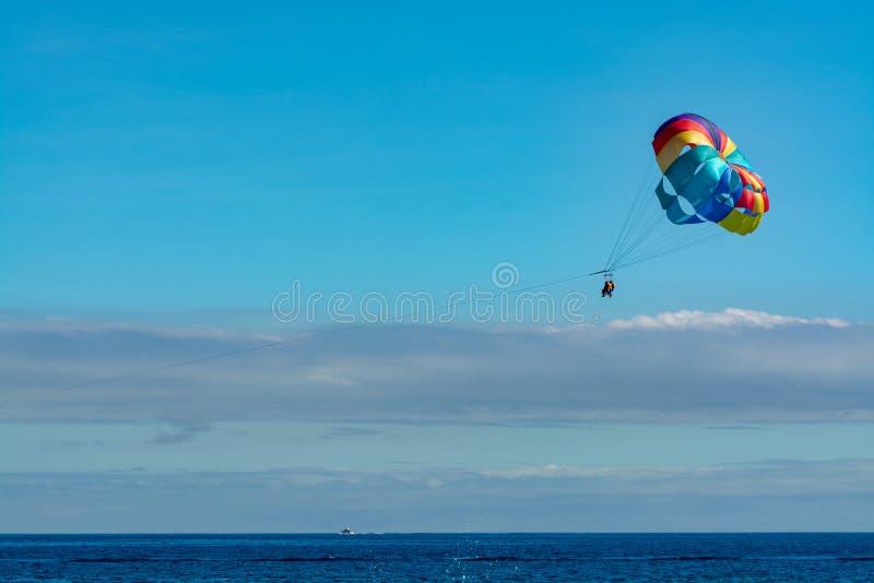 游人的海和海滩体育,在天空蔚蓝的帆伞运动 库存照片