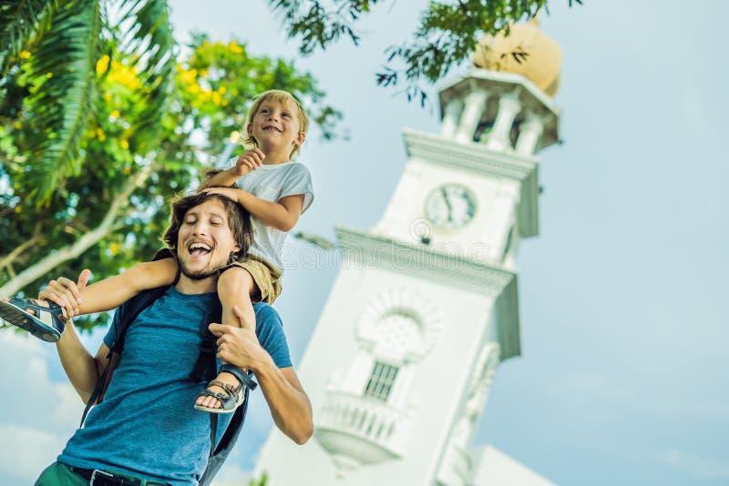 游人的父亲和儿子在女王维多利亚纪念钟楼,槟榔岛背景中  免版税库存图片