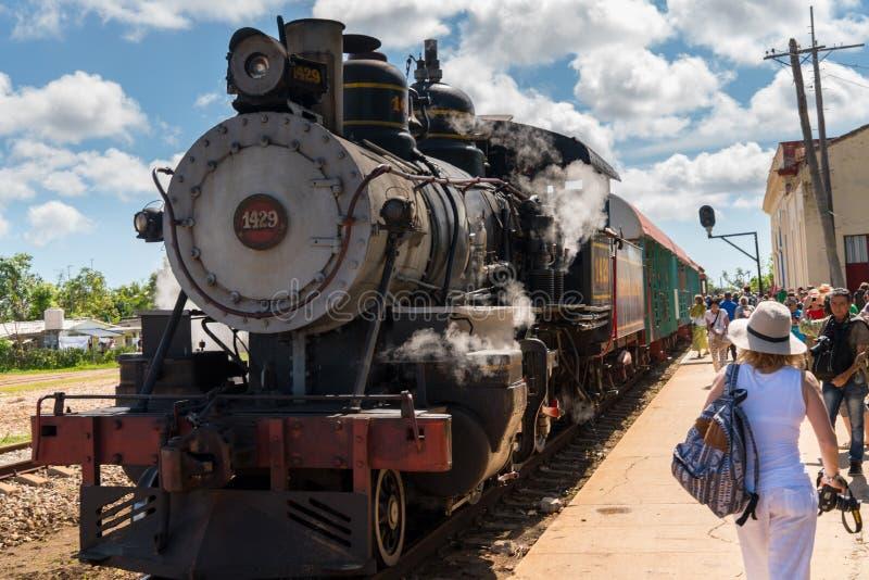 游人的老蒸汽火车ariive在驻地 免版税库存图片