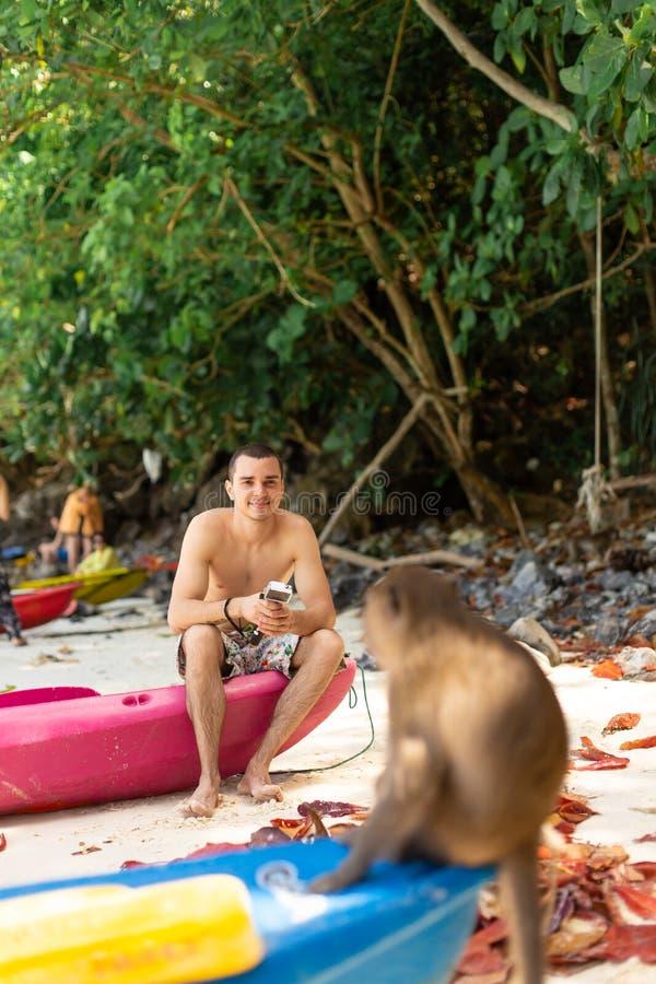 游人看猴子坐独木舟等待的食物的技巧从游人的 在热带海岛上的猴子海滩 库存照片