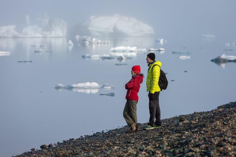 游人站立在黎明反对glasser盐水湖的背景雾的并且敬佩风景 免版税图库摄影