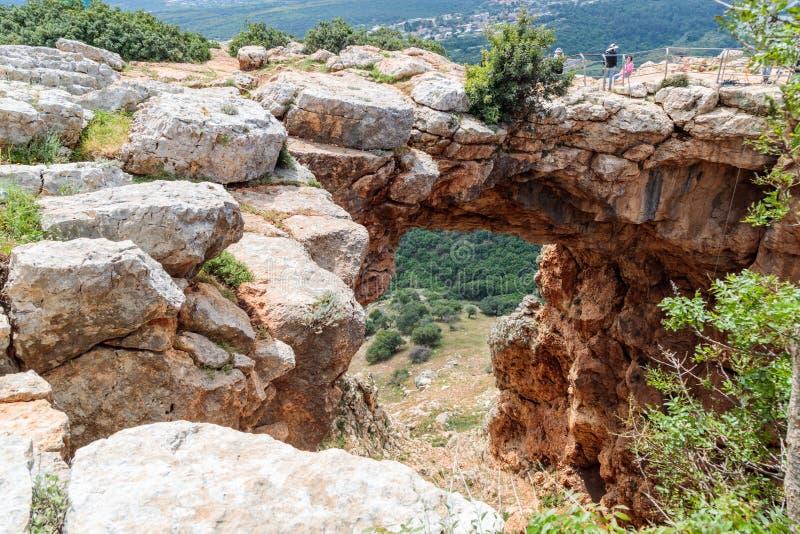 游人站立并且看Keshet洞-跨过一个浅洞的遗骸的与清扫v的古老自然石灰石曲拱 免版税库存图片