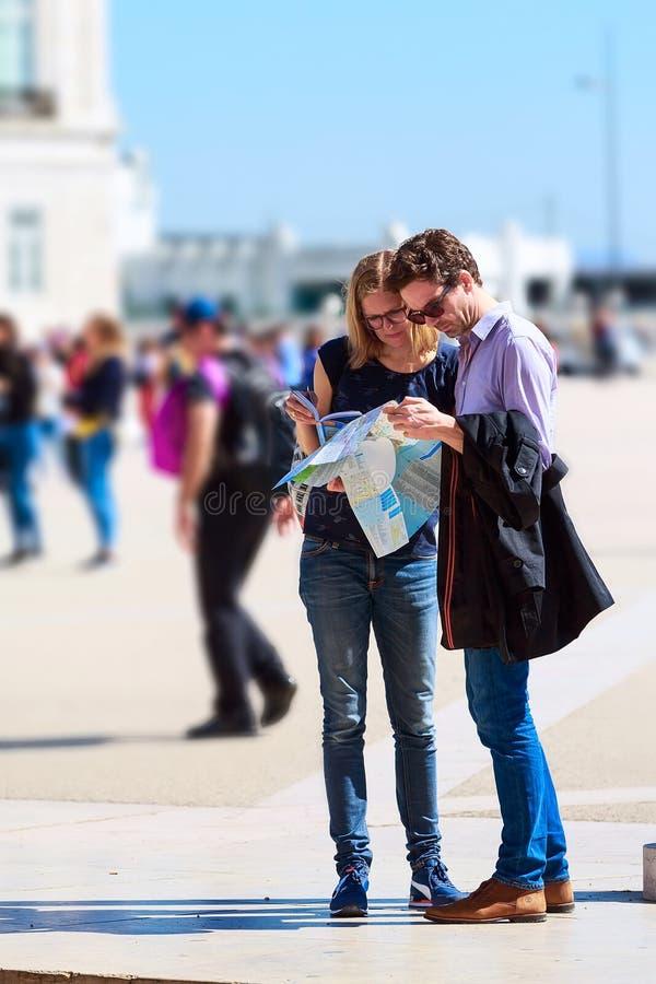 游人结合看城市地图 免版税库存图片