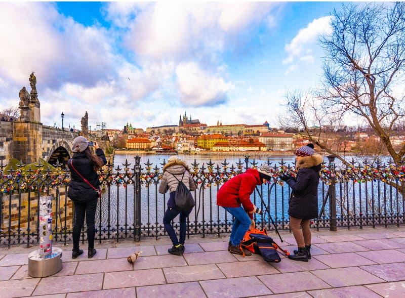 游人被拍布拉格城堡照片,在伏尔塔瓦河河的查尔斯桥梁附近 库存图片