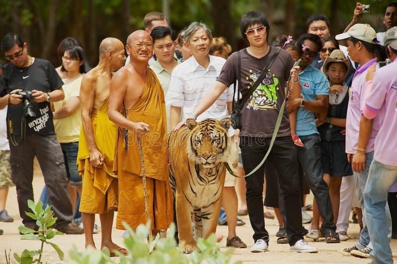 游人走与方丈处理的老虎Phra Acharn老虎寺庙的北碧,泰国Phoosit Khantidharo 库存照片