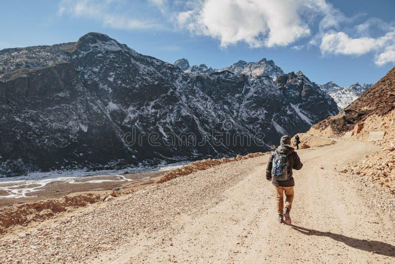 游人走染黑与雪的山在与议院的在黄色石地面的顶面和棕色山和冰河踪影 库存照片