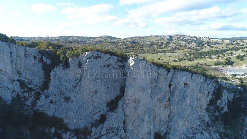游人顶视图在山深渊的 射击 岩石峭壁迷人的绿色植被看法和全景  组 免版税库存图片