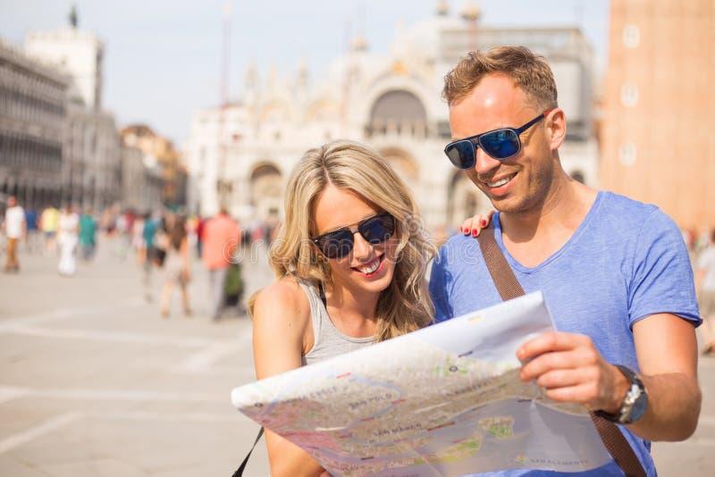 游人结合看城市地图 免版税图库摄影
