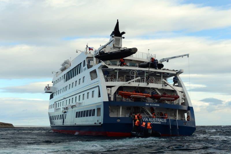 游人从游轮下船通过极光在马格达莱纳智利海岛上  免版税库存照片