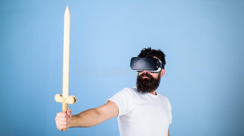游戏玩家概念 有头配显示器的人拿着剑,在VR的戏剧战斗的比赛 严肃的面孔的行家享受戏剧 库存照片