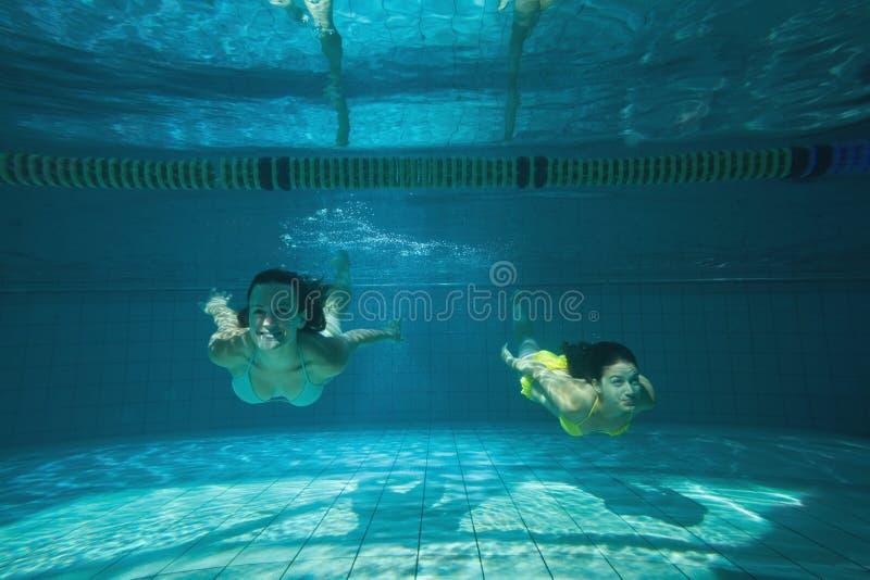 游泳俏丽的朋友微笑和在水面下 图库摄影