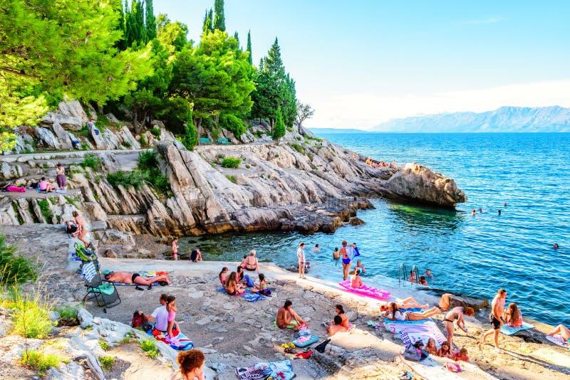 游泳和晒日光浴在岩石的人们在南克罗地亚 免版税库存照片