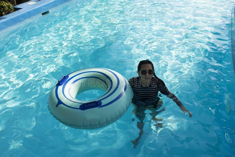 游泳和演奏在水池的泰国妇女水在室外 免版税库存图片