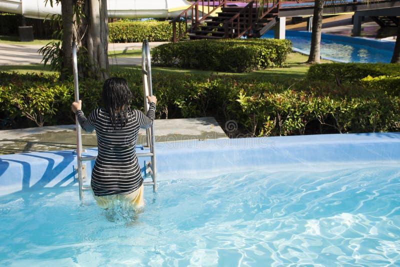 游泳和演奏在水池的泰国妇女水在室外 免版税库存照片
