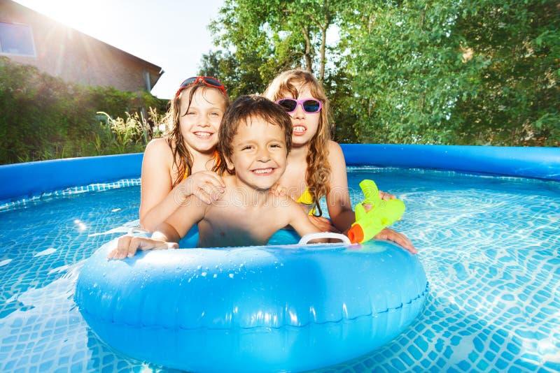 游泳在与橡胶环的水池的愉快的孩子 库存照片