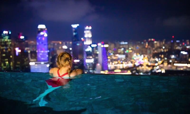 游泳在屋顶顶面室外水池的孩子家庭度假在新加坡 从无限水池的城市地平线在豪华旅馆里 孩子 免版税库存图片