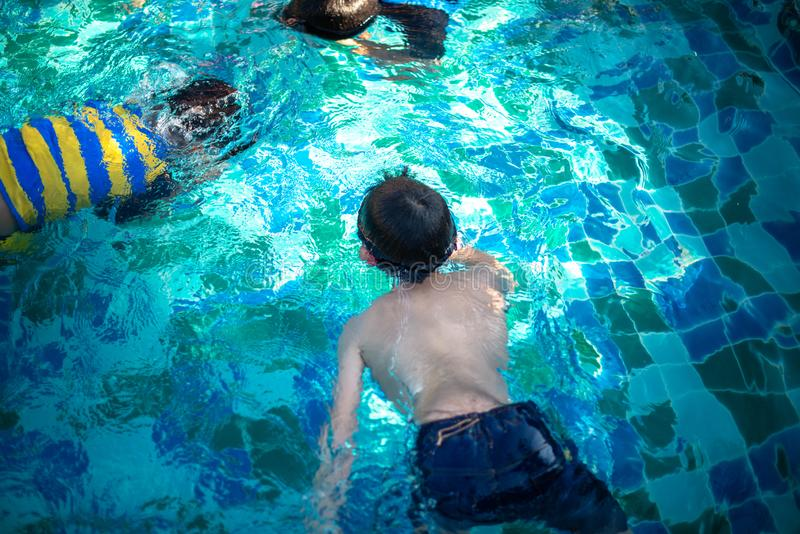 游泳在水池的孩子 免版税库存图片
